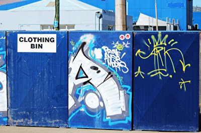 A photograph of street art on several clothing bin...